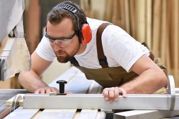 Tischler in einer Schreinerei sägt ein Holzbrett an einer Sägemaschine - Handwerker in Berufsbekleidung // Joiner saws a wooden board on a sawing machine - craftsmen in work clothing