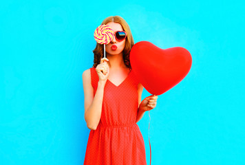 Portrait pretty woman with a lollipop candy, air balloon on blue background