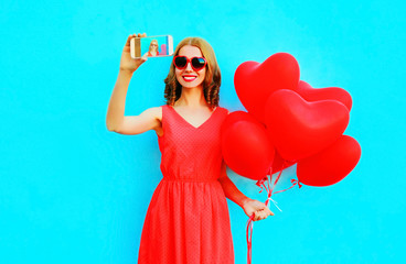 smiling woman takes a picture self portrait on a smartphone holds an air balloons on blue background