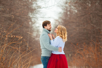 beautiful young couple in love, in light sweaters, walking in the park in cold weather