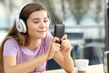 Relaxed teenager listening to music in an hotel bar