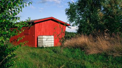 Gemütliche rote Hütte in grüner Landschaft