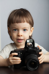 Beautiful child in with professional camera. Little boy with long blond hair photographing in the Studio