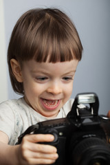 Beautiful child in with professional camera. Little boy with long blond hair photographing in the Studio. He looks at the resulting images on the camera and is happy