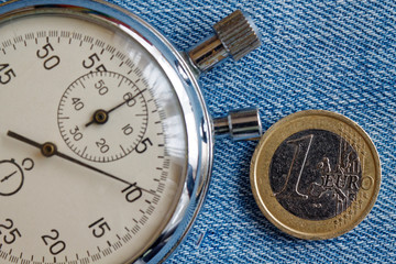 Euro coin with a denomination of 1 euro and stopwatch on blue denim backdrop - business background