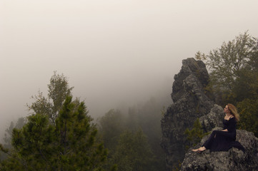 the red-haired barefoot girl in a black dress sits on a rock above the forest against the background of the approaching wall of fog