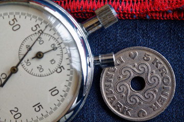 Denmark coin with a denomination of 5 krone (crown) and stopwatch on blue denim with red strip backdrop - business background