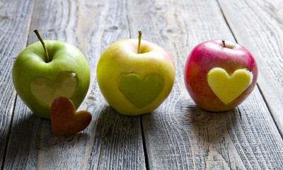 Apples with a cut heart on the wood
