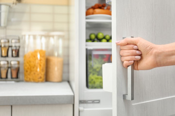 Woman opening refrigerator door, closeup