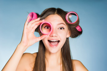 happy young girl wants to be beautiful, on her head and in her hands big pink curlers