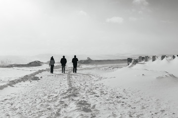 In the far cold north, three people walk along the snow-covered field