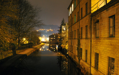 hebden bridge at night showing canal with the buildings of the town glowing in the distance