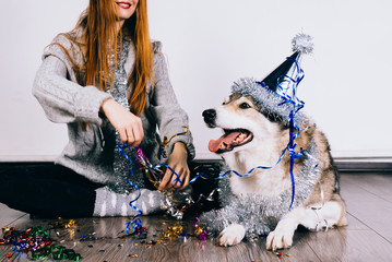 red-haired happy girl sitting on the floor with her big dog celebrating the new year and christmas