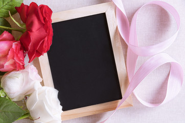 Blank blackboard and roses with ribbon - Unwritten chalkboard surrounded by beautiful colorful roses and a pink ribbon. Perfect frame for birthdays, mother day and valentine day.