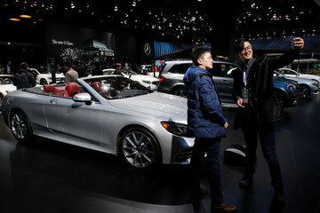 Visitors to the Mercedes booth take a selfie with the cars at the North American International Auto Show in Detroit, Michigan
