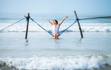 Pretty woman enjoy with ocean breeze and sun sits in hammock swing over the waves