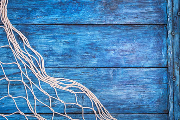 Old blue board with fishing net with copy space