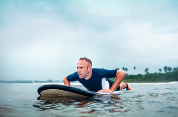 Surfer man floats on surf board, waits a waves