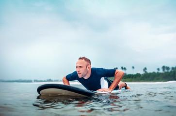 Surfer man floats on surf board, waits a waves