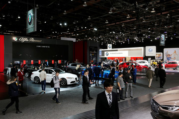 Visitors look at cars, including some in the Alfa Romeo booth, at the North American International Auto Show in Detroit, Michigan