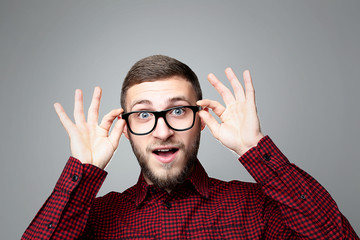Portrait of young surprised man in glasses on grey background