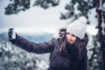 Beautiful woman with mobile phone snow landscape.