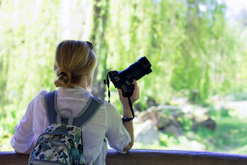photographer woman is standing and holding a camera, bright garden blurred background