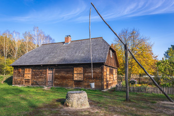 Old wooden traditional house and well sweep in heritage park of Kampinos Forest in Poland