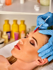 Filler injection for female forehead face. Plastic aesthetic facial surgery in beauty clinic. Beauty woman giving injections. Doctor in medical gloves with red syringe injects cheeks drug. Facelift.