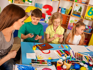 Plasticine modeling clay in children class. Teacher teaches kids together play dough and mold from plasticine in kindergarten or preschool. Group of four people. Newcomer in children's team.