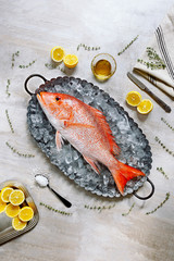 Top view raw fish red snapper or perch with lemon, salt, thyme