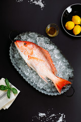 Top view raw fish red snapper or perch with lemon, salt, basil