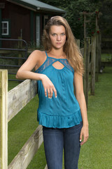 Beautiful teen girl poses in jeans and blouse on farm - rural setting