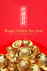 group of golden ingots on red tray at red background.Chinese new year concept,leave space for adding text.Chinese Language on ingot mean wealthy and lable mean May you have a prosperous New Year.