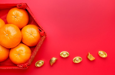 Group of orange tangerine in Chinese pattern tray with gold ingots on red table top. Chinese new year concep.Chinese Language ingot is wealthy.