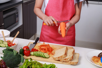 hand of woman peel carrots with a knife in kitchen room
