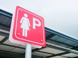 Lady parking sign in the gas station parking.