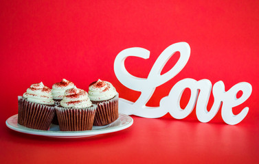 4 chocolate cupcakes with white frosting and red sprinkles on a white plate with a LOVE sign in cursive letters on a red background