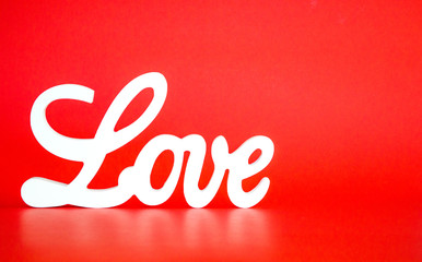 white LOVE sign in cursive letters on a red background with copy space