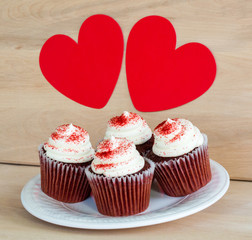 4 chocolate cupcakes with white frosting and red sprinkles on a wooden table with 2 red hearts above them