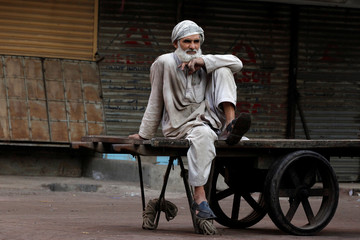 A laborer sits on a pushcart while waiting for work at a wholesale market early morning in Karachi
