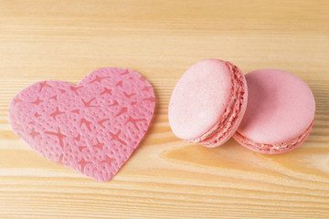 pink heart with two macaroni on a wooden background