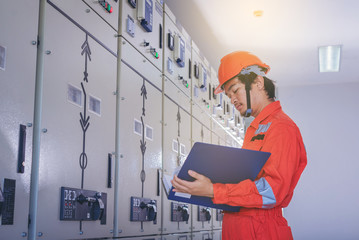 Electrical and instrument technician use manual guide to maintenance electric system for factory
