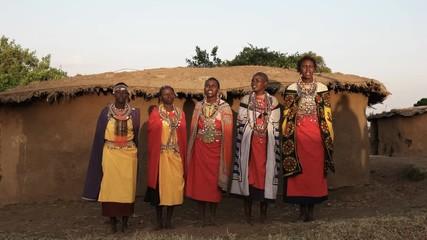 Wall Mural - wide shot of a group of maasai women singing in enkereri village near masai mara, kenya