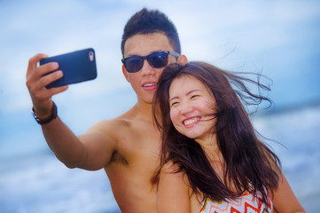 young happy and beautiful Asian Chinese couple taking selfie pho