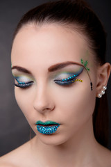 Brunette girl with fantasy makeup in blue tones on the eyes closed