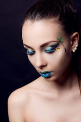 Portrait of glamorous brunette with fantasy makeup on the eyes closed on black background