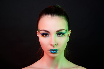 Glamorous brunette girl with fantasy make-up and coloured lights on the face on black background close-up