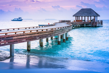 Wooden pier and blue sea at Maldives in sunset