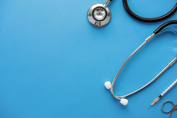 Medical instruments including stethoscope, scissors and syringe on light blue background, top view with copy space